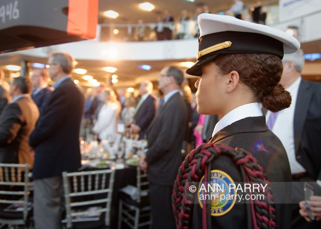 Garden City, New York, U.S. June 6, 2019. At right, a member of the Freeport High School Navy Junior ROTC is one of the cadets standing in front of the stage as Select Chorale members sing during Apollo at 50 Anniversary Dinner, an Apollo astronaut tribute celebrating the Apollo 11 mission Moon landing, at Cradle of Aviation Museum. Her uniform jacket has a braided epaulet on the left shoulder. (© 2019 Ann Parry/Ann-Parry.com)
