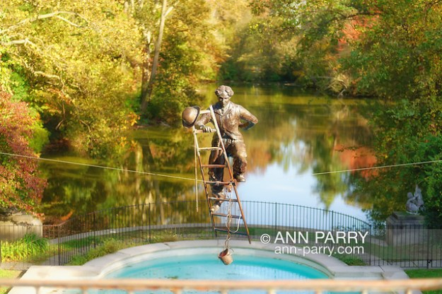 Old Westbury, New York, U.S. October 19, 2019. CHARLIE CHAPLIN sculpture suspended over reflecting pool is one of the Jerzy Kędziora (Jotka) Balance in Nature outdoor sculptures seen during the tour part of Closing Reception for the exhibit, held at Old Westbury Gardens. (© 2019 Ann Parry/Ann-Parry.com)