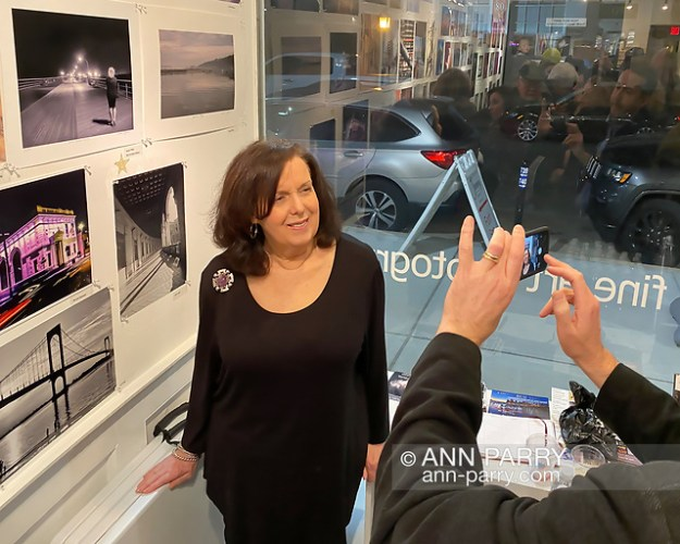 Huntington, New York, U.S. February 29, 2020. Susan Tiffen poses under to her photo 'Jones Beach Babe,' a Best in Show co-winner, as her son takes her picture during reception at fotofoto gallery for its 'Your Best Shot' Open Photography push-pin exhibition. (© 2020 Ann Parry/Ann-Parry.com)