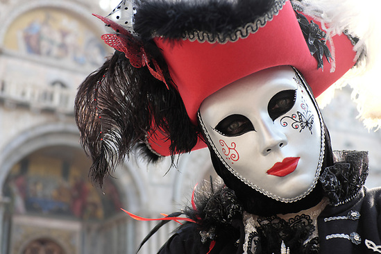 Woman dressed in traditional mask and costume for Venice Carnival standing in Piazza San Marco in front of Saint Mark's Basilica, Venice, Veneto, Italy (Brad Mitchell Photography)
