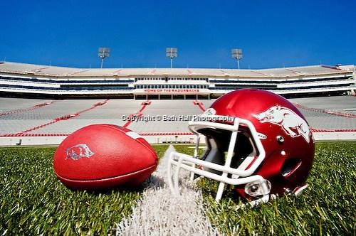 Arkansas Razorback football and helmet on the field at Donald W. Reynolds Razorback Stadium in Fayetteville, Arkansas (Beth Hall)
