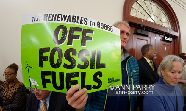 Mineola, NY, USA. Feb. 15, 2019. PHILIP MARINELLI, Huntington, is holding a green sign with 'Text Renewable to 69866' and 'OFF FOSSIL FUELS