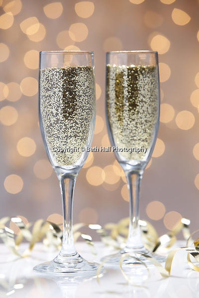 Stock photography of glitter filled champaign glasses with holiday lights. Photo by Beth Hall (Beth Hall)