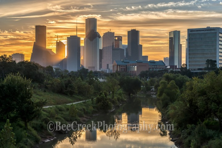 We were almost ready to leave and then sky turned into this golden swirling clouds over the skyline of the Bayou and city skyline so we had to take a few more images. You can see the sun just starting to peak through the high rise skyscrapers and the buildings reflections in the water of the Buffalo Bayou on this early morning sunrise. Watermark will not appear on image (Tod Grubbs)