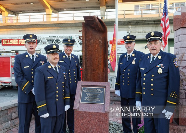 Bellmore, New York, USA. 11th September 2015. L-R, Bellmore Fire Dept. Chief DANIEL HOLL, Pastor and Chaplain JAMES BARNUM, 1st Deputy VINCENT MONTERA, 2nd Deputy TOM STOERGEN, and Chaplain DENNIS RICH stand next to a monument that's a piece of structural steel from the Twin Towers, during the Bellmore Memorial Ceremony for 3 Bellmore volunteer firefighters and 7 residents who died due to 9/11 NYC terrorist attacks. (© 2015 Ann Parry/Ann-Parry.com)