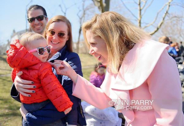 North Merrick, NY, USA. March 31, 2018. At right, Town of Hempstead Supervisor LAURA GILLEN chucks 8-month-old EMMA HALPERN under the chin, while Emma is held by her mom KELLY HALPERN, as dad MATT HALPERN looks on, at the Annual Eggstravaganza. (© 2018 Ann Parry/Ann-Parry.com)
