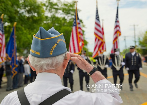 Merrick, New York, U.S. - May 26, 2014 - A veteran salutes fire fighters marching in The Merrick Memorial Day Parade and Ceremony, hosted by American Legion Post 1282 of Merrick, honors those who died in war while serving in the United States military. (Ann Parry/Ann Parry, ann-parry.com)