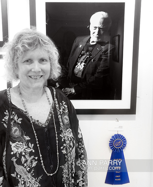 Manhasset, New York, U.S., September 8, 2019. Ann Parry poses next to her photo Buzz Aldrin - the 1st Place winner of The Art Guild's About Face: The Portrait juried competition, at Elderfields. photo courtesy Bob Stuhmer