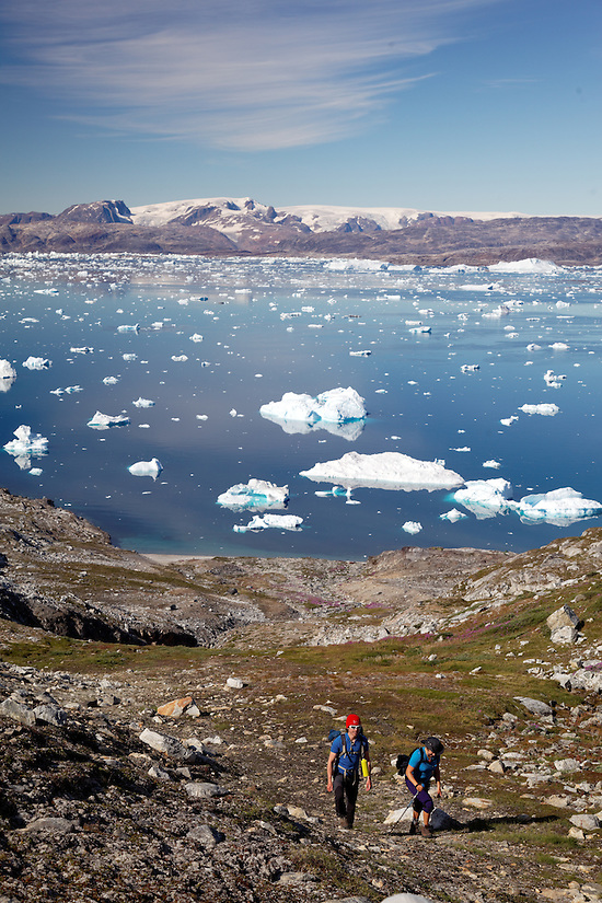 Hikers climbing up hill on edge of Sermilik Fjord near settlement of Tiniteqilaq, Greenland icecap in distance, East Greenland (Brad Mitchell)