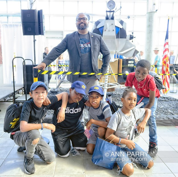 Garden City, New York, U.S. July 20, 2019. At top, New York State Senator KEVIN THOMAS poses with children from Westbury who attended Moon Fest Apollo at 50 Countdown Celebration at Cradle of Aviation Museum in Long Island, held during  same time Apollo 11 Lunar Module landed on the Moon 50 years ago. (© 2019 Ann Parry/Ann-Parry.com)
