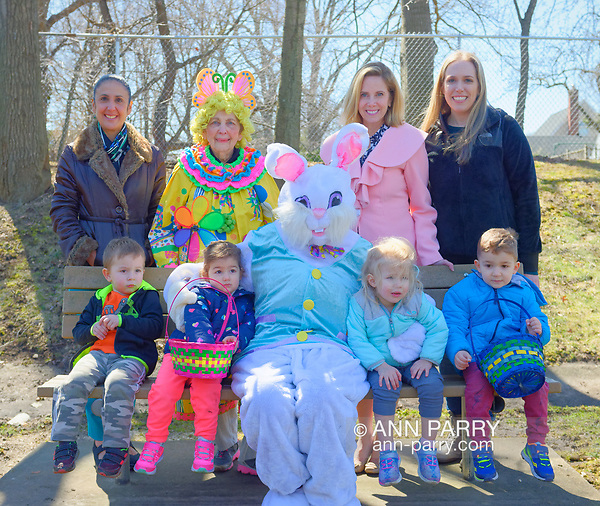 North Merrick, NY, USA. March 31, 2018. Back Row, L-R, Hempstead Town Clerk SYLVIA CABANA; BETTY TUCKER (clown) a member of American Legion Auxiliary Unit 1282; Hempstead Town Supervisor LAURA GILLEN; and SUE MOLLER, Co-President of North and Central Merrick Civic Association; pose with Easter Bunny and children at the Annual Eggstravaganza at Fraser Park. (© 2018 Ann Parry/Ann-Parry.com)