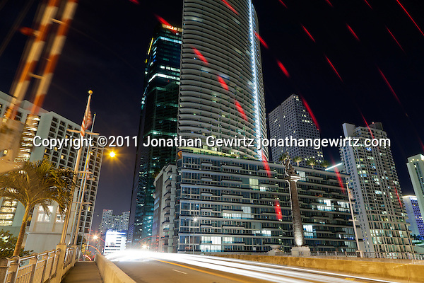Night view of the Brickell Avenue drawbridge over the Miami River as the pedestrian gate goes up, with condo and office buildings. (Jonathan Gewirtz)