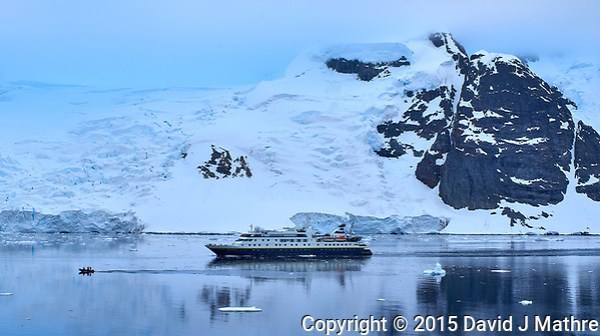 Zodiac Leading an Antarctic Cruise Ship Through the Lemaire Channel. I had never seen clouds this color blue before, and they were that color blue. I am guessing it is blue light reflecting off the glacier. Image taken with a Leica T camera and 18-56 mm lens (ISO 100, 31 mm, f/11, 1/40 sec). Image processed with Capture One Pro 8, Focus Magic, and Photoshop CC. (David J Mathre)