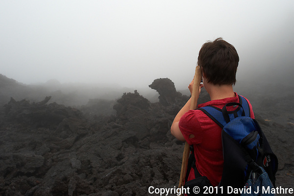 Hiker taking an image of the lava in the mist. On the trail to the Volcano. Pacaya Volcano National Park. Image taken with a Nikon D3x and 24 mm f/1.4G lens (ISO 320, 24 mm, f/8, 1/320 sec). Raw image processed with Capture One Pro and Photoshop CS5. (David J Mathre)