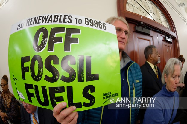 Mineola, NY, USA. Feb. 15, 2019. PHILIP MARINELLI, Huntington, is holding a green sign with'Text Renewable to 69866' and'OFF FOSSIL FUELS