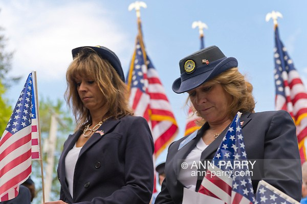 Merrick, NY, USA. May 26, 2014 - L-R, MARGARET BIEGELMAN and DEBRA BERNHARDT, members of the Merrick American Legion Auxiliary Post 1282, bow their heads during a moment of silence for those who died in war while serving the U.S. military - during The Merrick Memorial Day Ceremony. (© 2014 Ann Parry/Ann-Parry.com)