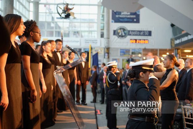Garden City, NY, U.S. June 6, 2019. Freeport High School Select Chorale singers perform - with their Director MONIQUE RETZLAFF standing at right, facing them - during Apollo at 50 Anniversary Dinner. FHS Navy Junior ROTC cadets are saluting. Apollo astronaut tribute celebrating the Apollo 11 mission Moon landing was held at Cradle of Aviation Museum.) (© 2019 Ann Parry/Ann-Parry.com)