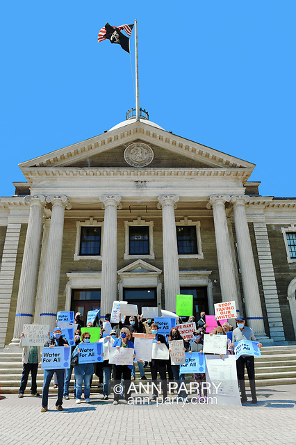 """Mineola, NY, USA. April 26, 2021. Activists and civic leaders - including in front row, center, wearing lapis blue face mask and jacket, CLAUDIA BORECKY, a Co-Director of CAWS (Clean Air Water Soil) - rally at Theodore Roosevelt Executive and Legislative Building. Faced with a 26% rate increase from New York American Water going into effect May 1, 2021, activists and residents who are NYAW customers rally. (© 2021 Ann Parry/AnnParry.com)"