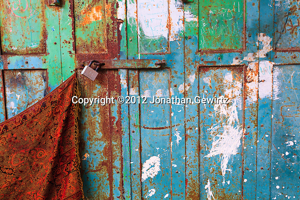 Closeup view of a colorful, rusty, locked metal door on a shop front in the Old City of Jerusalem. (© 2012 Jonathan Gewirtz / jonathan@gewirtz.net)