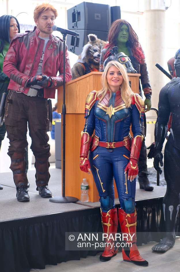 Garden City, NY, U.S. July 20, 2019. At right is SAMANTHA CATALANO as Captain Marvel, at left wearing red jacket is DOM CHARLAND as Peter Quill or Star-Lord, and upper right with red hair and green face is EYLIZA MORCIGLIO as Gamora - three Marvel super heroes in The NY Avengers non profit cosplay group, during Moon Fest Apollo at 50 Countdown Celebration at Cradle of Aviation Museum in Long Island at time Apollo 11 Lunar Module landed on Moon 50 years ago. (© 2019 Ann Parry/Ann-Parry.com)