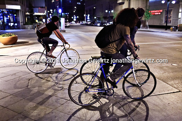 Three young men on bicycles cross a busy intersection at night in downtown Denver, Colorado. (Jonathan Gewirtz)