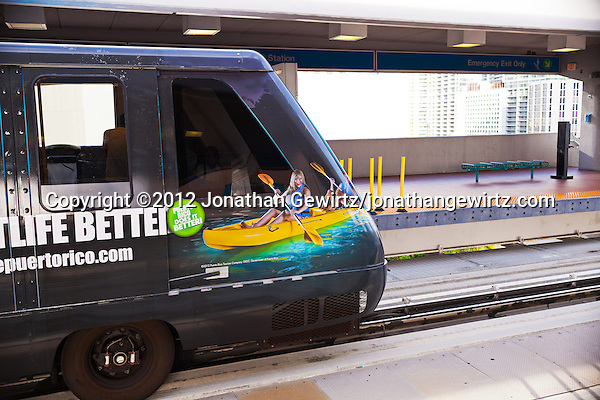 An automated rail car with a vivid photographic advertisement on its exterior departs a downtown Miami Metromover station. (© 2012 Jonathan Gewirtz / jonathan@gewirtz.net)