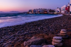 Mykonos beach at sunset with Little Venice in background