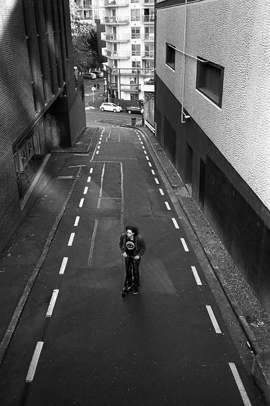 Lone scooter rider in alley | Nikon RD2 | Ilford FP4 Plus