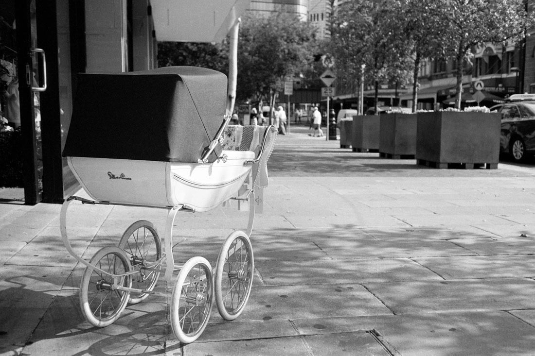 Pram on street |Topcon RE Super | Topcor 3.5cm f/2.8 RE Auto | Ilford FP4 Plus
