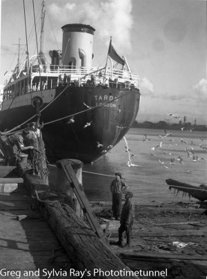 Workers repair a damaged wharf, with  the ship Taron in the background