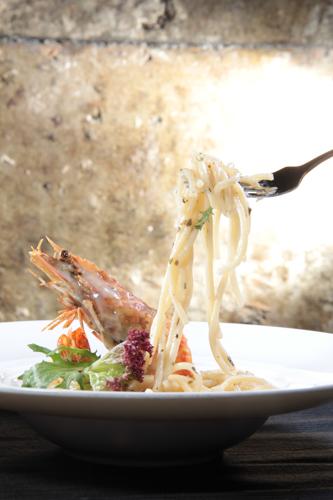 フォークを使ってエビのハーブホワイトソーススパゲッティを拾う