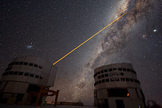 Shooting a Laser at the Galactic Centre: The sky above Paranal on 21 July 2007. Two 8.2-m telescopes of ESO's VLT (Very Large Telescope) are seen against the wonderful backdrop of the myriad of stars and dust that makes the Milky Way. Just above Yepun, Unit Telescope number 4, the Small Magellanic Cloud - a satellite galaxy of the Milky Way - is shining. A laser beam is coming out of Yepun, aiming at the Galactic Centre. It is used to obtain images that are free from the blurring effect of the atmosphere. On this image, the laser beam looks slightly artificial. This is a side effect due to saturation caused by the long exposure time. Planet Jupiter is seen as the brightest object on the upper right, next to the star Antares. Image taken by ESO astronomer Yuri Beletsky.<br />