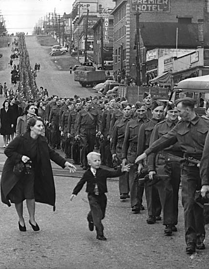 Wait for Me, Daddy, taken by Claude P. Dettloff, a Vancouver Daily Province photographer. British Columbia Regiment, (Duke of Connaught's Own Rifles), marching in New Westminster, British Columbia, Canada, 1940.