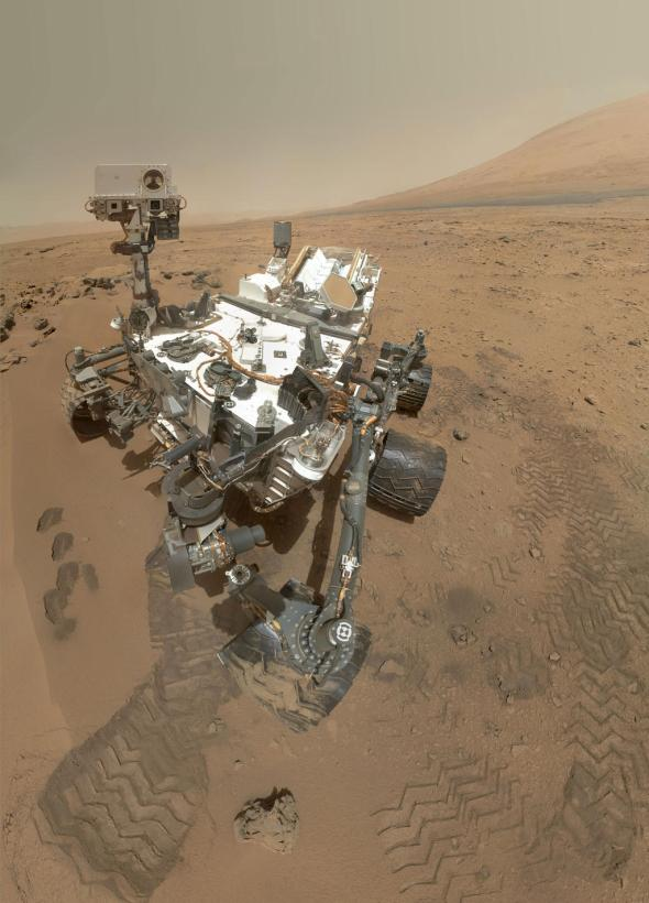 """""""High-Resolution Self-Portrait by Curiosity Rover Arm Camera On Sol 84 (Oct. 31, 2012), NASA's Curiosity rover used the Mars Hand Lens Imager (MAHLI) to capture this set of 55 high-resolution images, which were stitched together to create this full-color self-portrait. The mosaic shows the rover at """"Rocknest,"""" the spot in Gale Crater where the mission's first scoop sampling took place. Four scoop scars can be seen in the regolith in front of the rover. The base of Gale Crater's 3-mile-high (5-kilometer) sedimentary mountain, Mount Sharp, rises on the right side of the frame. Mountains in the background to the left are the northern wall of Gale Crater. The Martian landscape appears inverted within the round, reflective ChemCam instrument at the top of the rover's mast. Self-portraits like this one document the state of the rover and allow mission engineers to track changes over time, such as dust accumulation and wheel wear. Due to its location on the end of the robotic arm, only MAHLI (among the rover's 17 cameras) is able to image some parts of the craft, including the port-side wheels."""" Image Credit: NASA/JPL-Caltech/Malin Space Science Systems."""