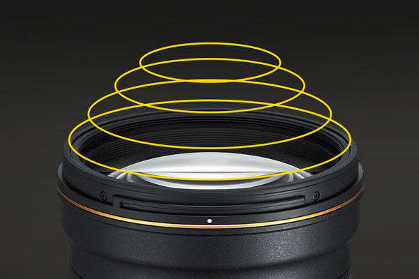 """""""The Phase Fresnel optical design appears to have a series of concentric circles engraved on it, and these circles each focus a different spectrum and direction of light. The result is a substantially lighter, more compact lens with outstanding optical performance and prevention against ghosting and chromatic aberration."""" Image Courtesy of Nikon"""