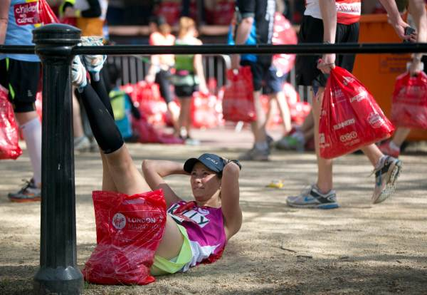 A participant stretches her legs after completing the London Marathon April 13, 2014. REUTERS/Neil Hall (BRITAIN - Tags: SPORT ATHLETICS) Picture Supplied by Action Images