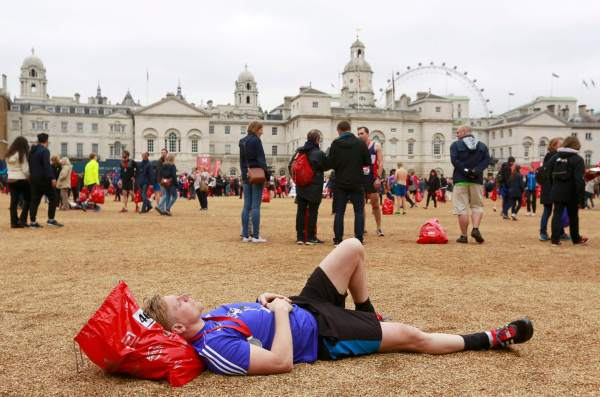 A runner rests on the gravel of Horse Guards Parade after finishing the London Marathon, April 26, 2015. REUTERS/Cathal McNaughton Picture Supplied by Action Images