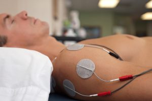 Physical therapy or chiropractic treatment of a male patient's injured shoulder using transcutaneous interferential electrical stimulation (TENS) for pain management.