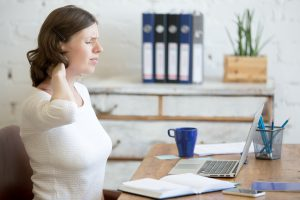 Young stressed businesswoman sitting in front of laptop and holding her neck with pained expression. Business woman feeling pain touching aching neck suffering from neck ache after long work on pc