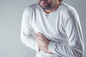 Severe abdominal pain man suffering from stomach ache holding his belly and having painful cramps.