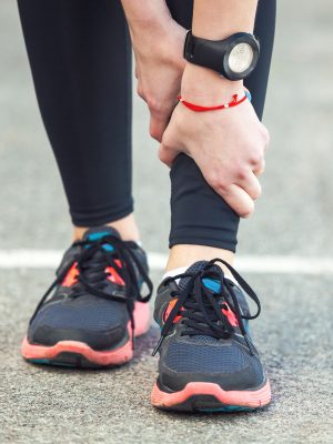 Young female runner is holding her injured leg. Shin splint problem.
