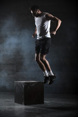 Athlete gave exercise. Jumping on the box. Phase touchdown. Studio shots in the dark tone. ** Note: Soft Focus at 100%, best at smaller sizes