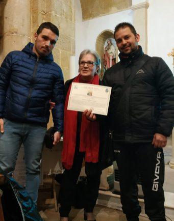 Lucia Fiammata consegna il premio al presidente del Comitato Festa Santa Cristina Benito Carrozza