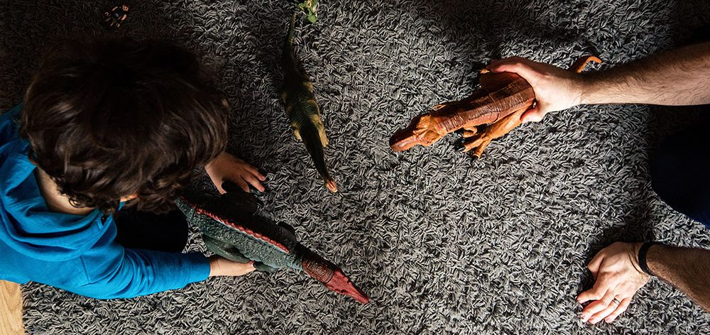 son and dad playing on the floor with dinosaurs from documentary photography session