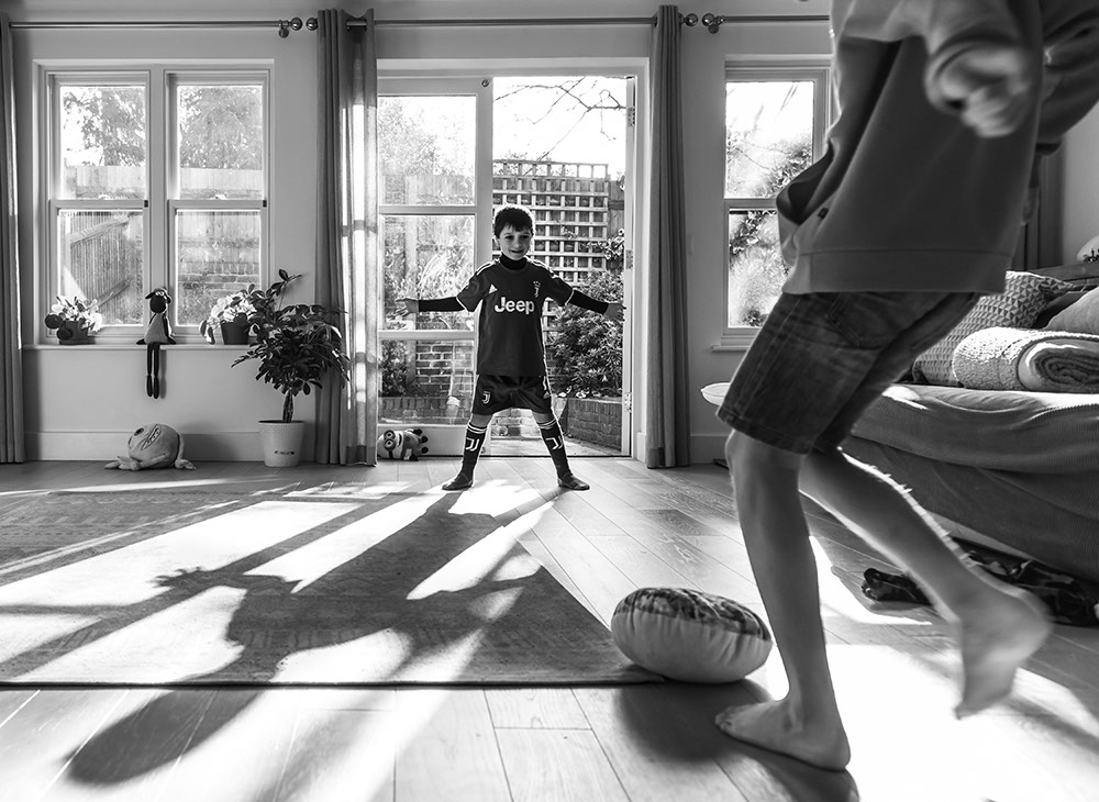 sibling playing football at home by documentary family photographer - Piccolino Photo Studio