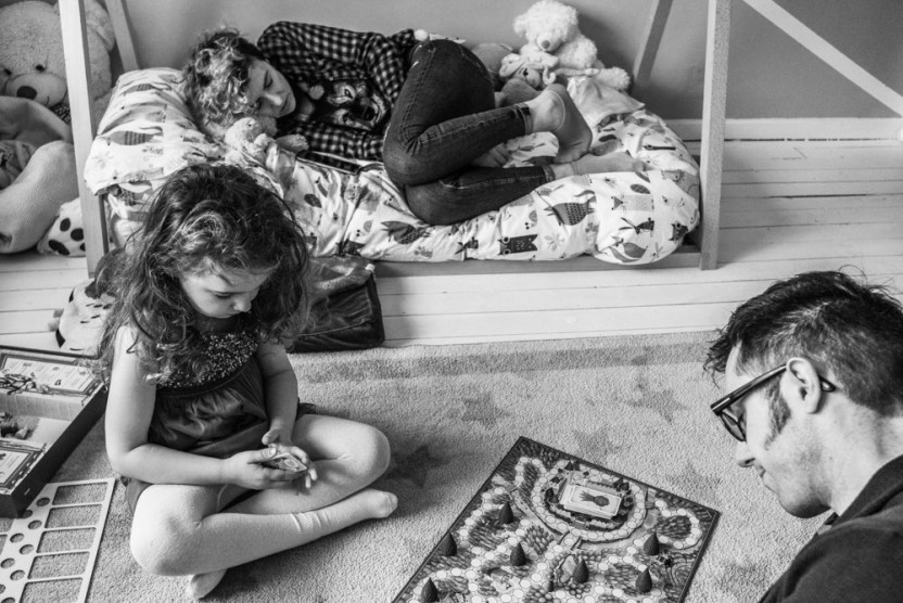 Dad and daughter playing a board game while mum relaxes on her daughter bed by documentary family photographer