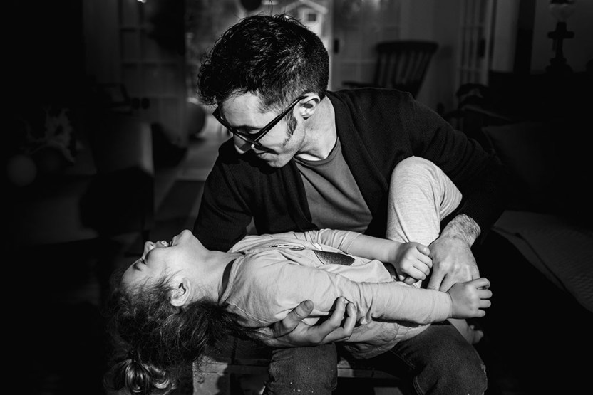 Sweet moment between daughter and her dad black and white by documentary photographer in London