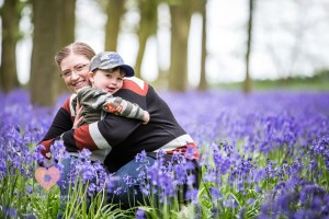 Mum and and son cuddle in the bluebells.