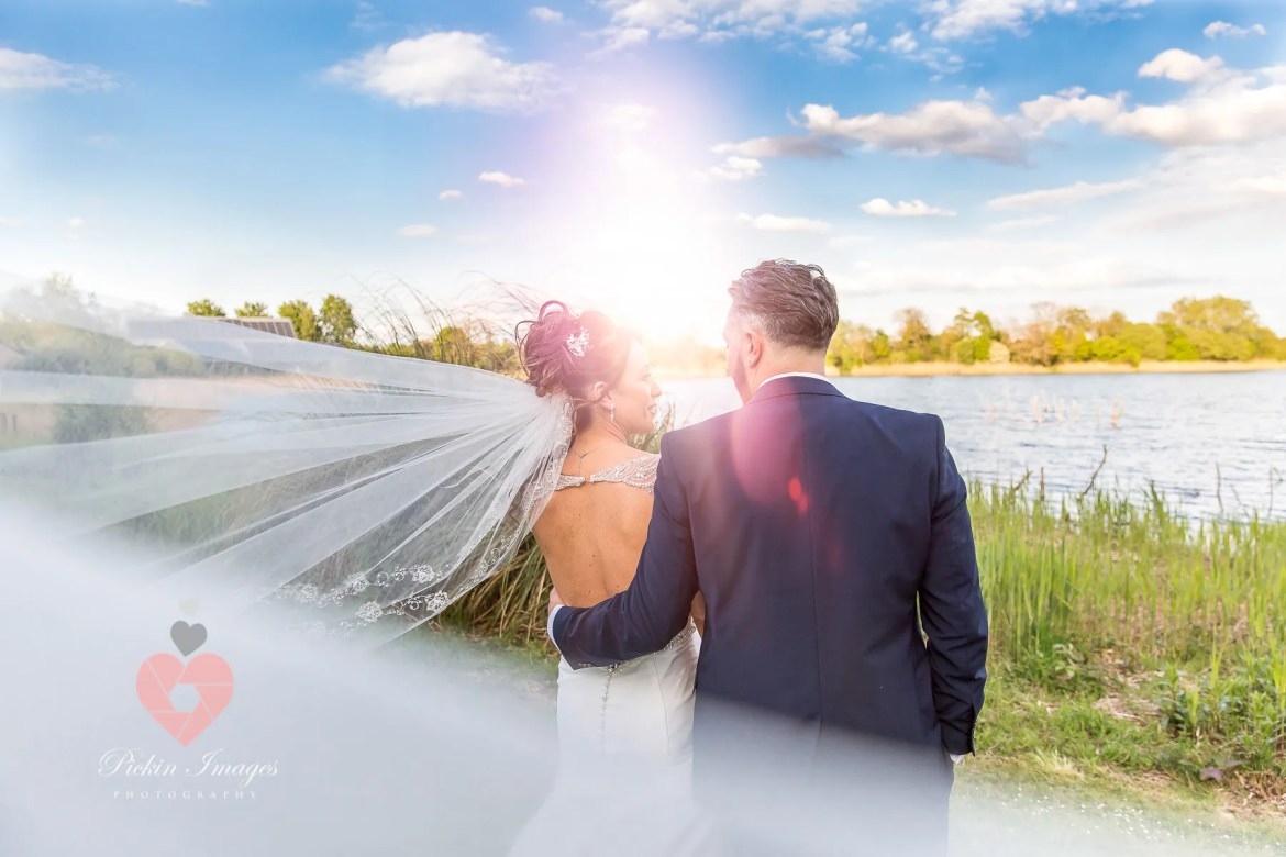 Wedding photo at De Vere Four Pillars Hotel. Bride and groom by the lakes | wedding photographer in Swindon, Wiltshire