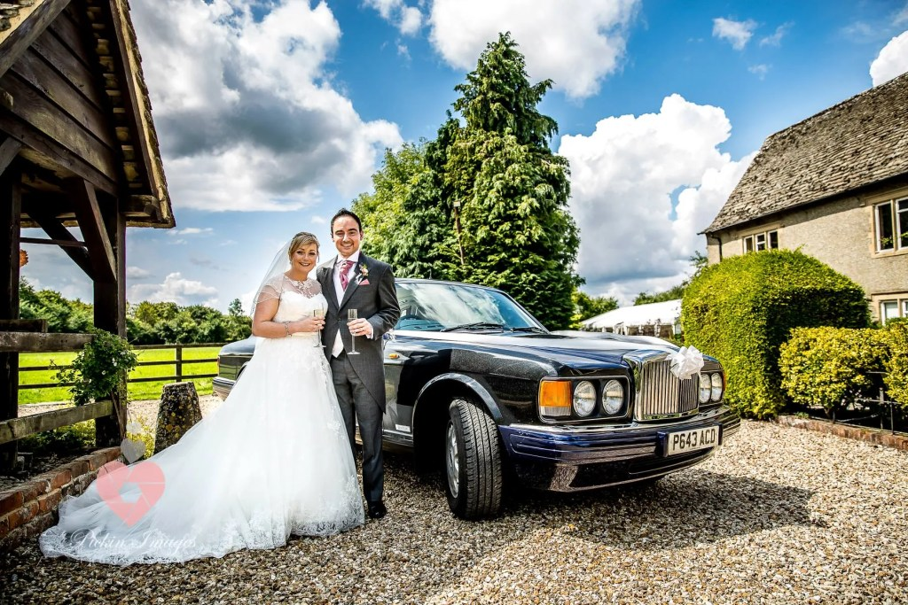 Bride and groom stood by the wedding car RR fathers car